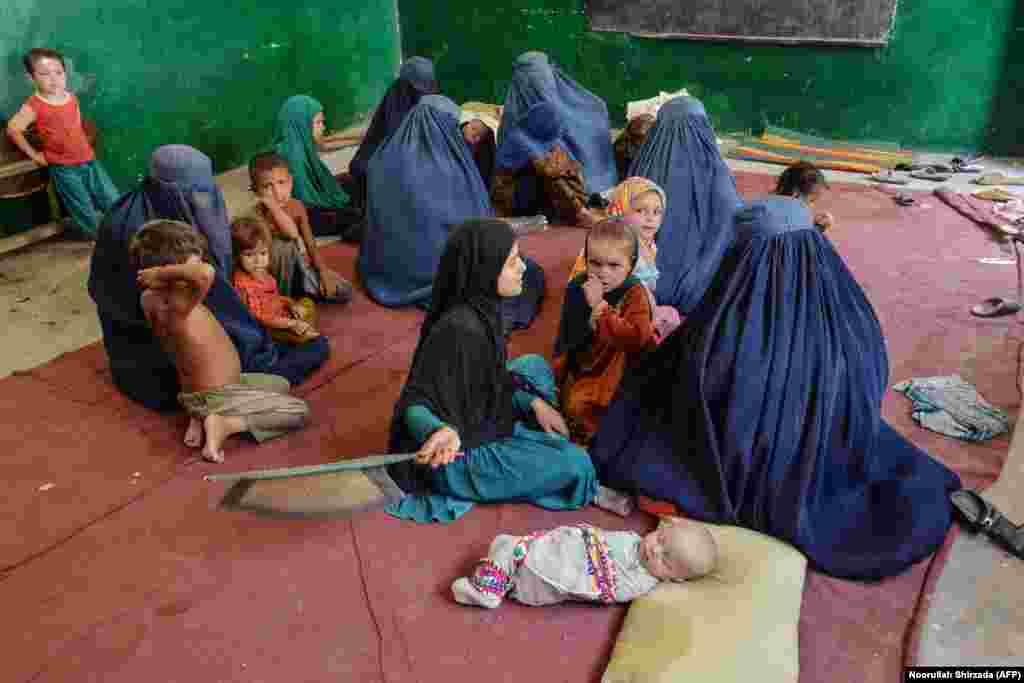 Жанчыны і дзеці адпачываюць у школе ва ўсходняй афганскай правінцыі Кунар 7 жніўня пасьля таго, як пакінулі свае дамы, каб схавацца ад баёў.