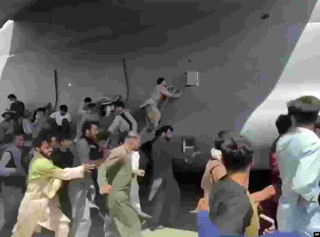 Афганистанци се опитват да се качат на американски самолет на летището в Кабул.
