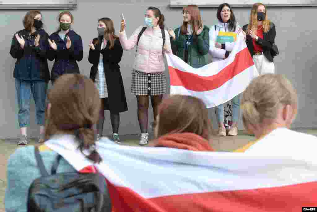 Students display the red and white colors of the opposition -- adopted from a flag flown during Belarus's short-lived bid for democratic independence more than a century ago.
