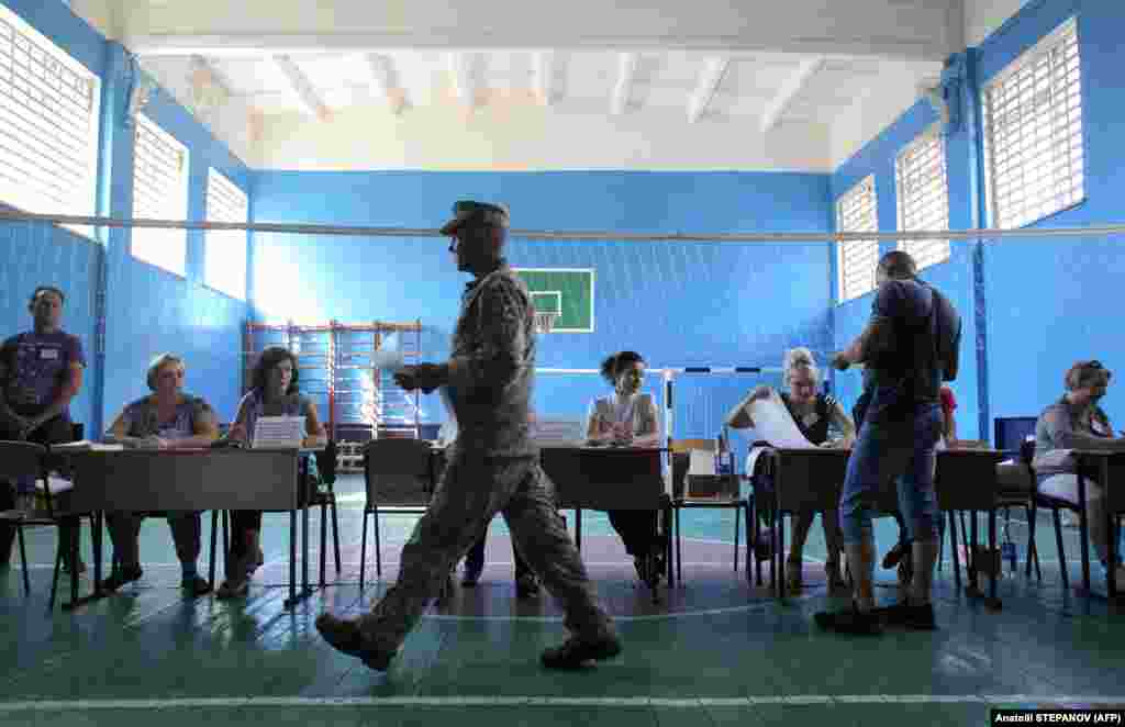 A Ukrainian serviceman holds his ballot as he walks to cast his vote at a polling station in the town of Avdiivka. (AFP/Anatolii Stepanov)