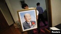 Последователь Муна несет его портрет к алтарю во время поминальной церемонии в Церкви объединения