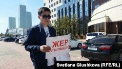 Молодой человек с листовкой «Жер сатылмасын» («Нет продаже земли») у здания столичного акимата в день, когда активистами планировалась акция протеста «по земельному вопросу», проведение которой местные власти не разрешили. Астана, 21 мая 2018 года.