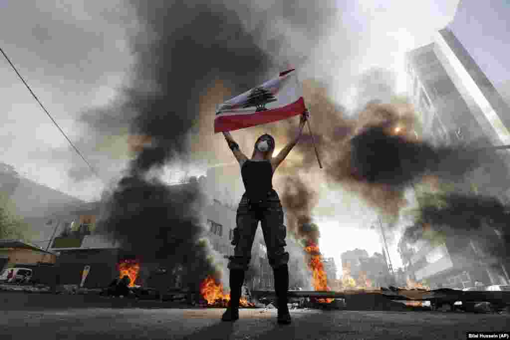 An anti-government protester holds a Lebanese flag while standing in front of burning tires blocking a road in the town of Jal el-Dib, north of Beirut. (AP/Bilal Hussein)