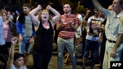 Armenia -- Armenian opposition supporters shout and gesture in front of riot police blocking the streets to Erebuni police station seized by gunmen - supporters of fringe jailed opposition leader Zhirayr Sefilian - in Yerevan early, July 28, 2016
