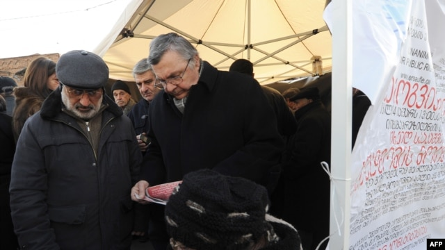 Georgian opposition supporters collect signatures for a petition asking for the resignation of President Mikheil Saakashvili near his office in central Tbilisi on January 4.