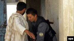 A policeman frisks a man as he enters a polling station in a high school in Kandahar Province on August 19.