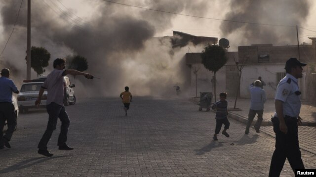 Smoke rises over the streets after a mortar shell landed from Syria in the border village of Akcakale on October 3.