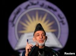 Ауғанстанның биліктен кететін президенті Хамид Карзай дауыс берген саусағын көрсетіп тұр. Кабул, 5 сәуір 2014 жыл.