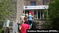 Люди входят в здание офиса «Инвестиционной строительной компании КВАРТИРЫ НС-М.С.-7». Астана, 5 августа 2015 года.