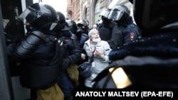 Rendőrök visznek egy tiltakozót egy nem engedélyezett tüntetésről Szentpéterváron, Oroszországban, 2021. január 31-én.
