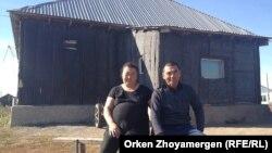 Оралмандар Сәния Сәкеш пен Бақытбек Азамат (оң жақта) үйлерінің алдында отыр. Қоянды, 22 қыркүйек 2013 жыл.