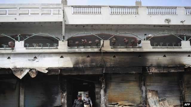Pakistani police investigate the site of a burned market in a violence-hit western neighborhood of Karachi of July 8.
