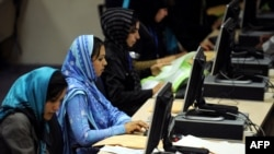 Election workers count votes at their computer terminals at the Independent Election Commission headquarters in Kabul.