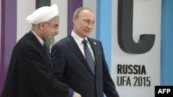 Russia -- Russian President Vladimir Putin (R) welcomes Iranian President Hassan Rohani during the 7th BRICS summit in Ufa, July 9, 2015