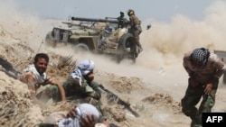 Iraqi pro-government forces fire an antitank cannon near the Al-Sejar village northeast of Fallujah on May 25.