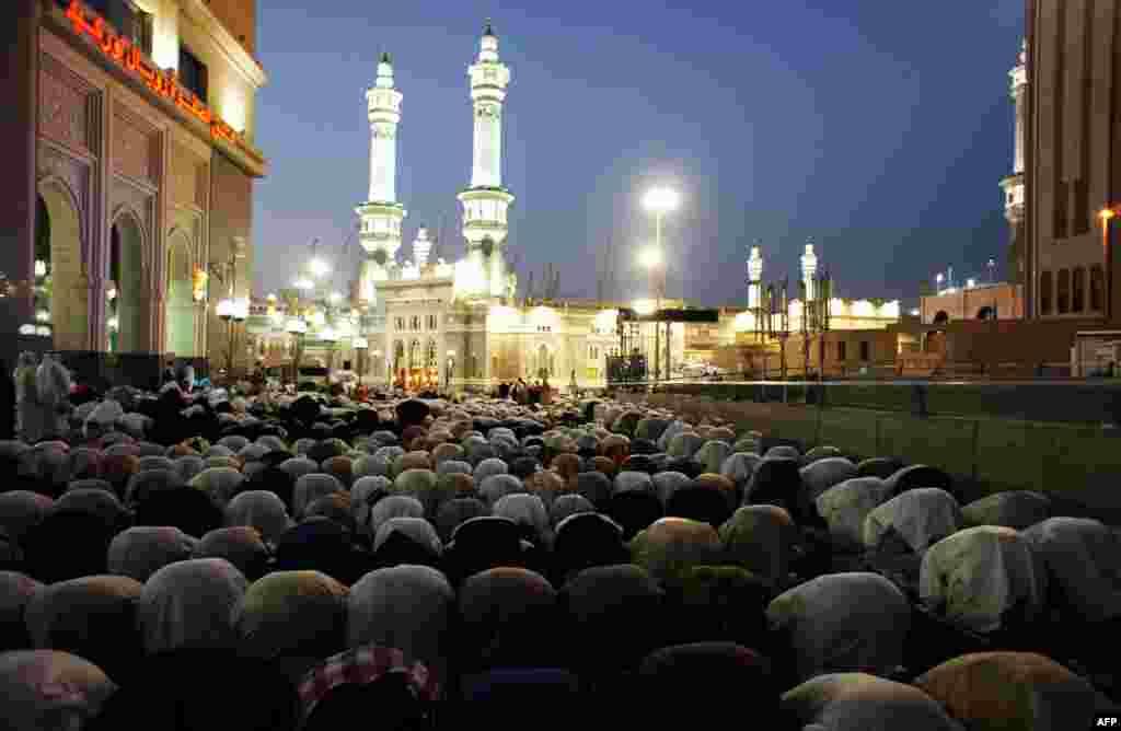 Muslim pilgrims perform the evening prayer near the Grand Mosque. (AFP PHOTO/MUSTAFA OZER)