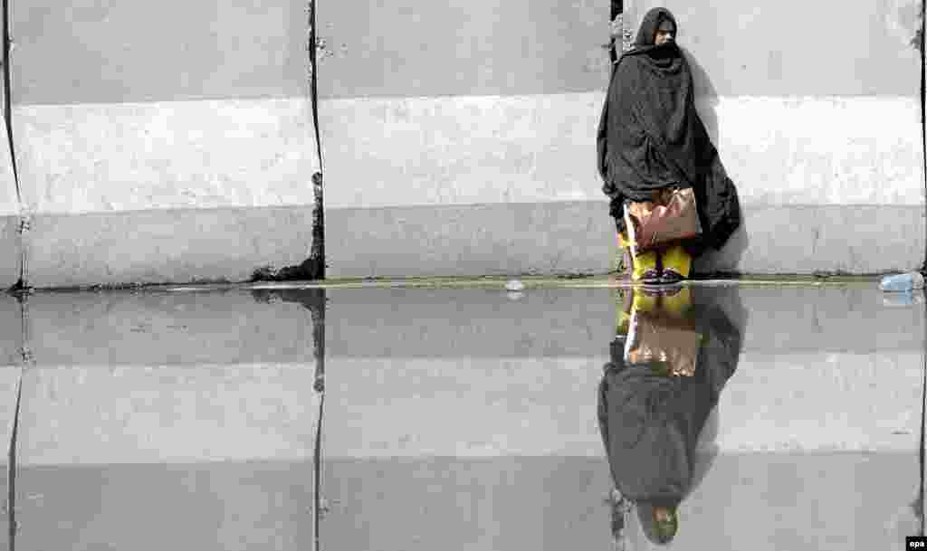 A Pakistani woman is reflected in a puddle of water as she waits to cross an inundated road in Islamabad on June 23. (epa/T. Mughal)