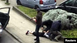 Belgium -- Police officers detain a suspect during a raid in which fugitive Mohamed Abrini was arrested in Anderlecht, near Brussels, April 8, 2016