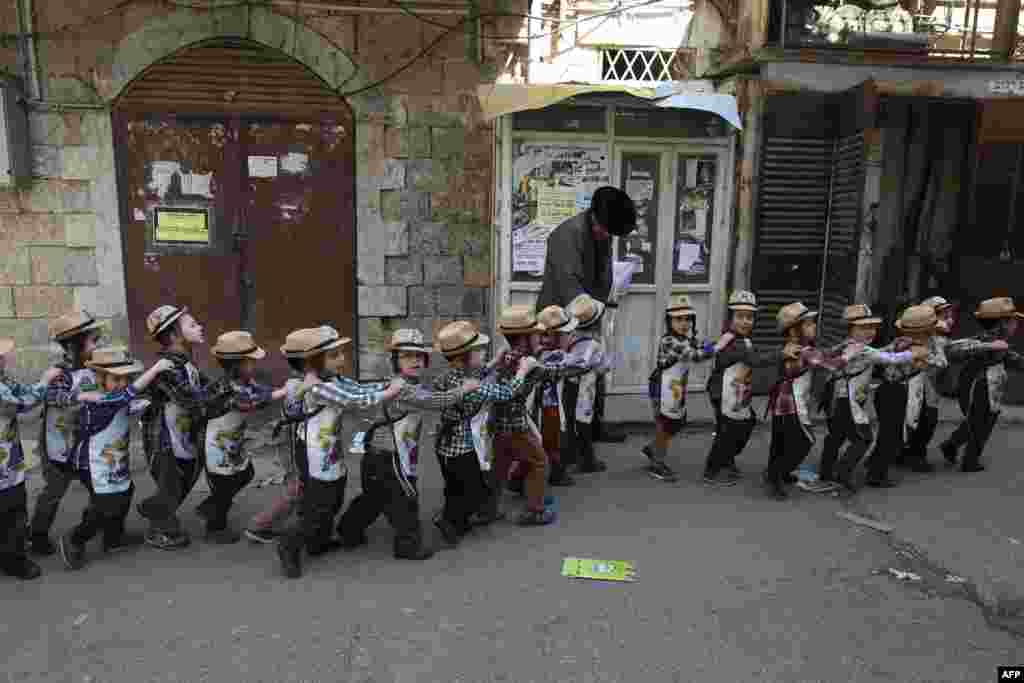 Ultra-Orthodox Jewish children wearing costumes march in line during their school Purim celebration ahead of the official holiday in the ultra-Orthodox Jewish neighborhood of Mea Shearim in Jerusalem. The carnivallike Purim holiday is celebrated with parades and costume parties to commemorate the deliverance of the Jewish people from a plot to exterminate them in the ancient Persian empire 2,500 years ago, as recorded in the Biblical Book of Esther. (AFP/Menahem Kahana)