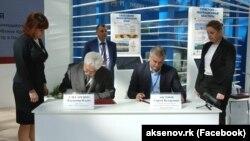 Cергей Аксенов (слева) подписывает инвестсоглашение с директором ООО «Эколого-туристический центр в Парковом»