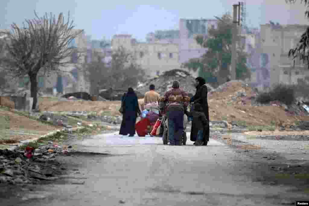 People carry their belongings as they flee the Kadi Askar area toward the Bustan al-Qasr neighborhood in besieged, rebel-held Kadi Askar area of Aleppo, Syria, on December 5. (Reuters/Abdalrhman Ismail)