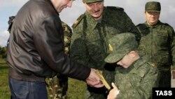 Коля Лукашенко разглядывает подаренный золотой пистолет