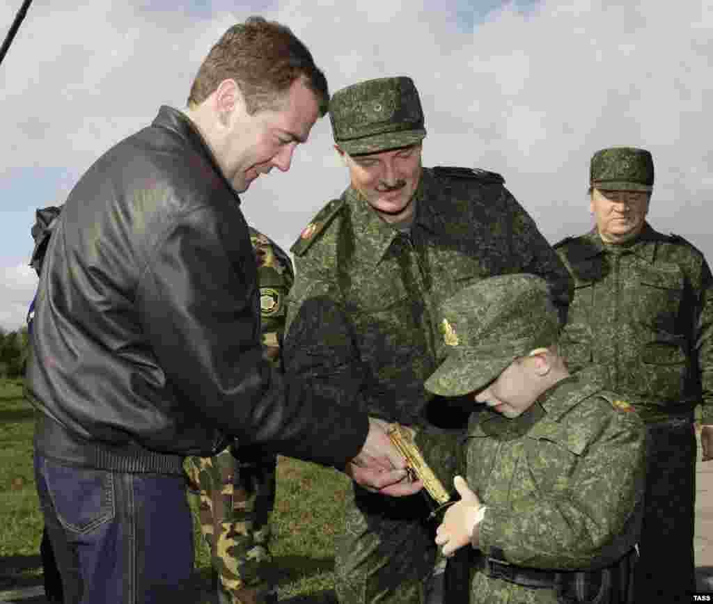 Президент России Дмитрий Медведев (слева), его белорусский коллега Александр Лукашенко и пятилетний сын президента Беларуси Николай. 2009 год. Мальчик кладет в карман золотой пистолет, подарок Медведева.