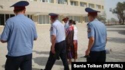 Полицейлер құқық қорғаушы Әсел Нұрғазиеваны әкімдікке апара жатыр. Жаңаөзен, 29 маусым 2012 жыл.