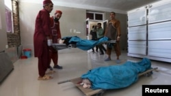 Afghan medical workers carry the bodies of two foreign women who were shot dead in Herat on July 24.