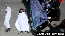 Afghan men wearing clothes spattered in blood lay down on a road as protesters shout slogans against the Iranian regime and demand justice during a protest outside the Iranian Embassy in Kabul on May 7.