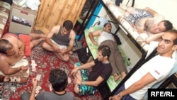Iranian immigrants pass the time in a crowded hostel room in Dubai