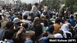 Авганистански цивили чекаат во близина на аеродромот во Кабул за да заминат од земјата