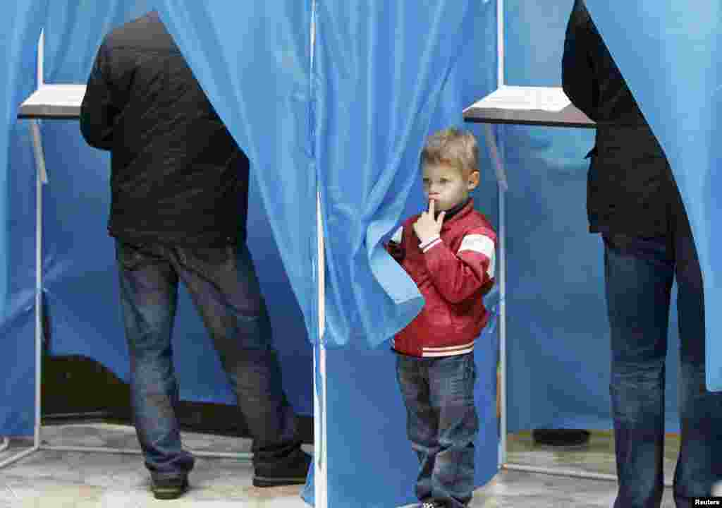 A boy peers from behind a curtain at a polling station in Kyiv.