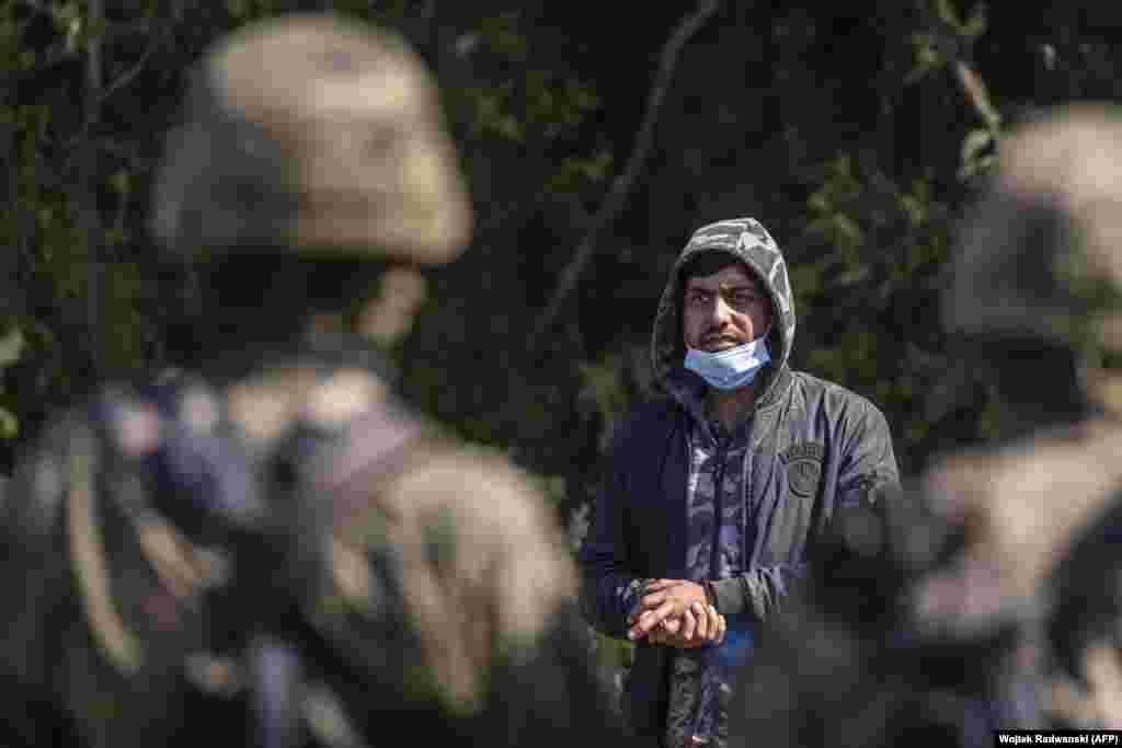 A stranded migrant seen behind Polish servicemen.  Defense Minister Mariusz Blaszczak announced on August 23 that Poland would be erecting a fence along the border with Belarus and that troop numbers stationed to deal with the border influx would be doubled to 2,000.