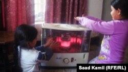 طفلان حول مدفأة في منزل ببغداد