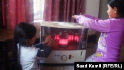 طفلتان بجوار مدفأة نفطية في احد المنازل ببغداد