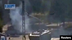 A video grab from a social media website on August 3 shows smoke rising near a tank at Al-Bahra roundabout in Hama.