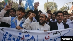 Student supporters of Jamaat-e Islami hold a banner and shout anti-American slogans in Peshawar on November 29 during a protest over the NATO air strikes three days earlier.