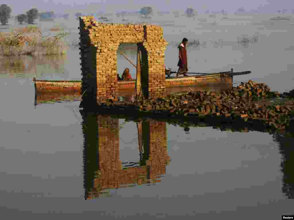 Pakistani flood victims on a boat pass by a doorway left standing after floods destroyed houses in the village of Chandan Mori Johi, in Sindh Province, on September 30. Photo by Athar Hussain for Reuters