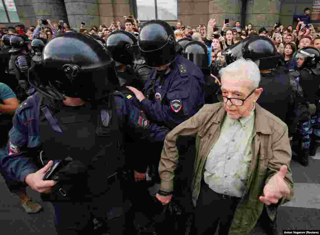 An elderly man being detained by police. The man later apparently collapsed.