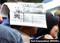 """Мужчина, прикрывший голову газетой """"Жас Алаш"""", наблюдает за акцией протеста активистов оппозиции. Алматы, 28 апреля 2012 года."""