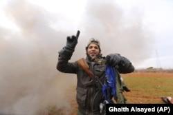 Боец одной из антиасадовских группировок, обороняющих Идлиб, держит в руках детали летного комбинезона пилота, управлявшего сбитым Ми-8 армии Асада. 11 февраля 2020 года