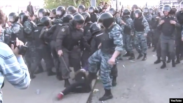 A YouTube video shows a Russian OMON officer kicking a woman in the abdomen during May 6 antigovernment protests.