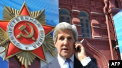 U.S. Secretary of State John Kerry talks on a cell phone as he walks on May 7 in front of a giant poster marking the upcoming Victory Day on the Red Square in Moscow.