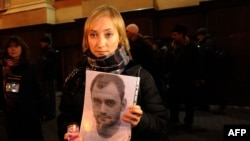Darya Korsak, the wife of the imprisoned Alyaksandr Atroshchankau, holds her husband's portrait during a protest in front of the headquarters of the Belarusian KGB in Minsk less than a month after the disputed presidential election of December 2010.