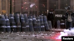 Polisiýa işgärleri protestçileriň daş we ot zyňyp edýän hüjümlerinden ýörite galkanlar bilen goranýarlar. Aleksandriýa, 25-nji ýanwar, 2013.
