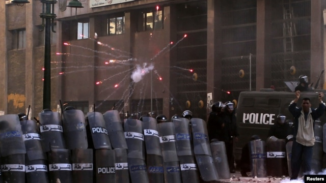 Egyptian riot police take cover as protesters throw flares and stones during clashes in Alexandria on January 25.