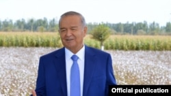 Uzbek President Islam Karimov stands in front of his country's biggest export.