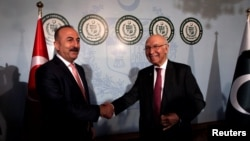 Turkish Foreign Minister Mevlut Cavusoglu (L) shakes hands with Adviser to Pakistan's Prime Minister on National Security and Foreign Affairs, Sartaj Aziz in Islamabad on August 2.