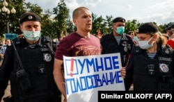 Un protestatar la Moscova, cu o pancarta pe care scrie Smart Voting, august 2021.